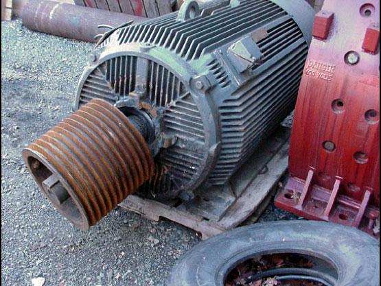 failed industrial electric motor sitting on asphalt